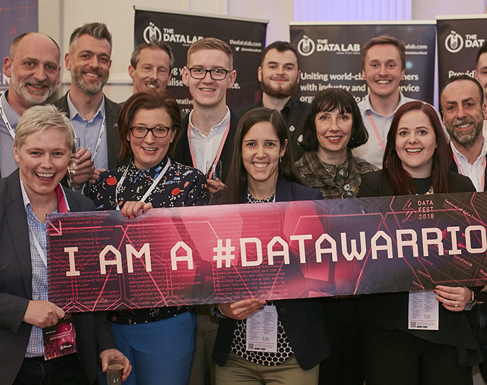 The Data Lab team holding I am a #DataWarrior banner