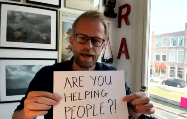Man holding sign that says Are you helping people?